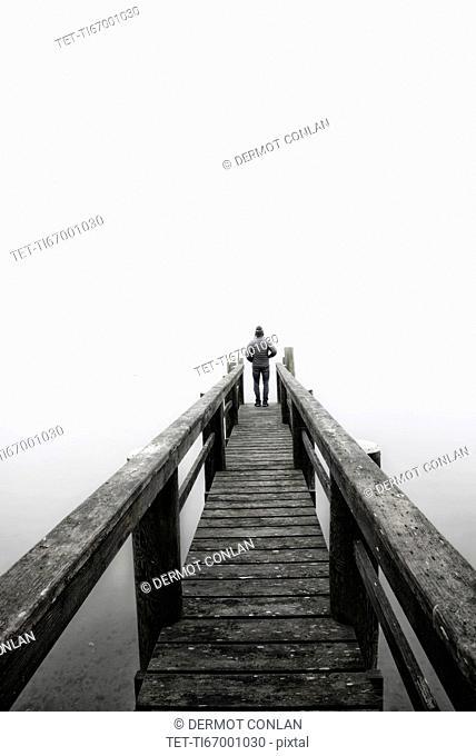 USA, Massachusetts, Cape Cod, Eastham, Man standing on jetty in fog