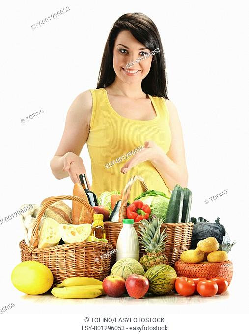 Young woman with groceries in wicker basket isolated on white