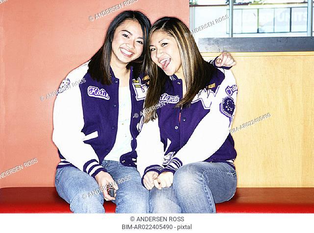 Portrait of two teenage girls wearing letterman's jackets