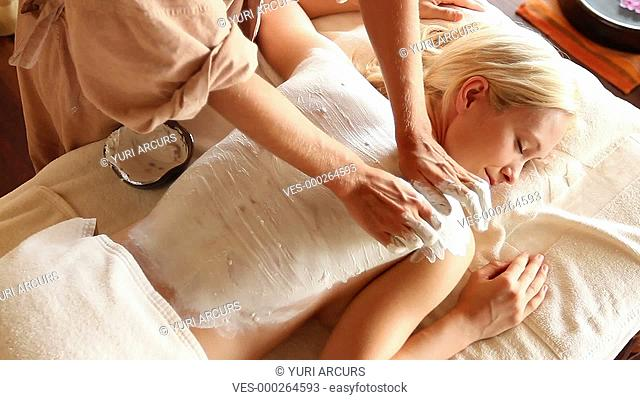 Topview of a woman receiving a professional clay treatment for her back
