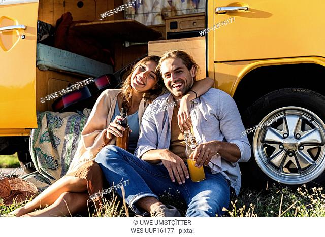 Affectionate couple on a road trip, taking a break, drinking soft drinks