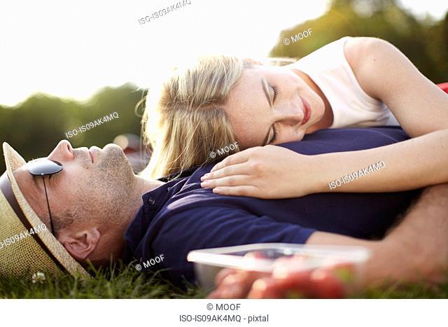 Couple lying asleep in park