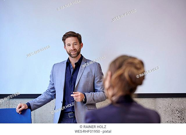 Coach talking to woman in training room
