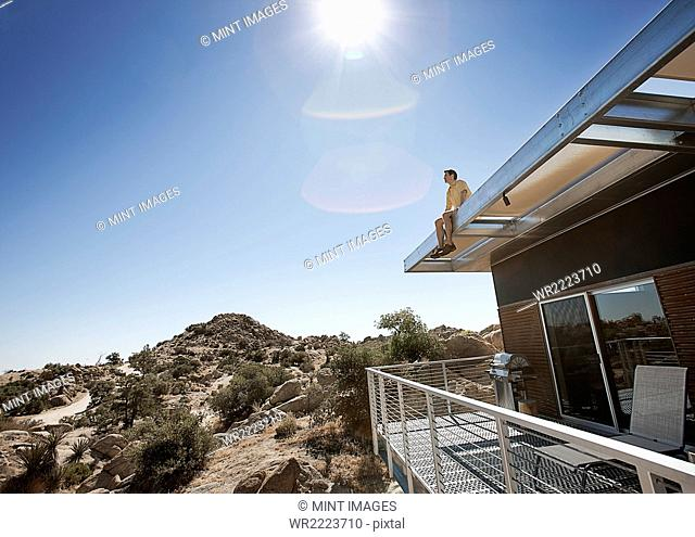 A man sitting on the roof overhang of an eco home in the desert landscape