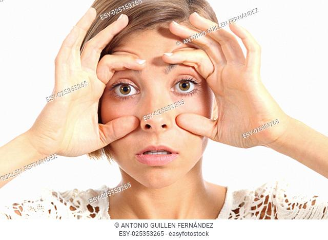 Tired woman opening her eyes with the fingers isolated on a white background