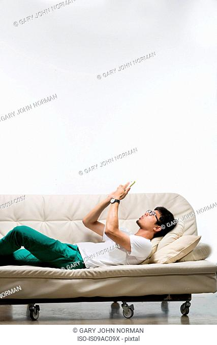 Young man lying on sofa using smartphone