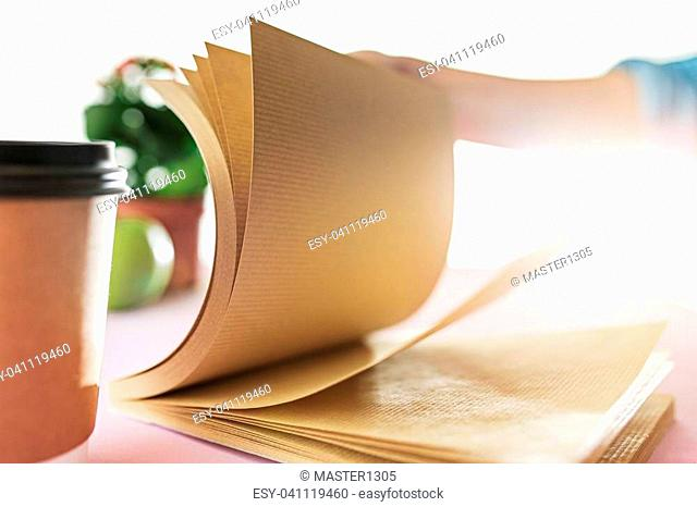 The business woman in the workplace flipping through the dailybook. Side view on woman on trendy color pink desk. Woman and stilish workplace