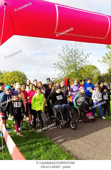 Crowd ready at charity run starting line in park