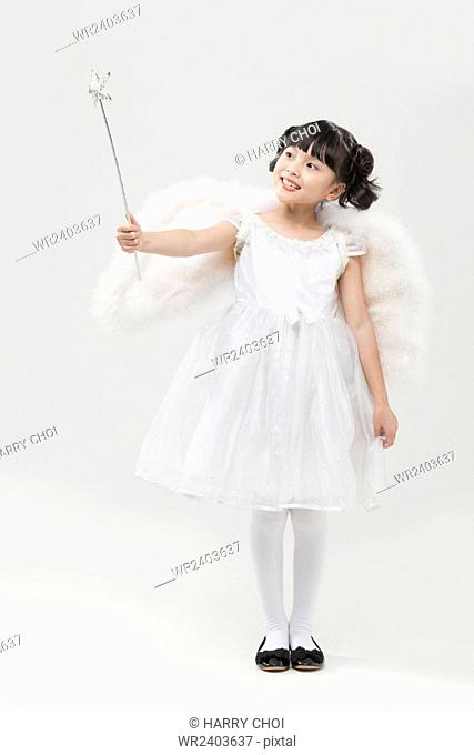 Smiling girl dressed like an angel looking up