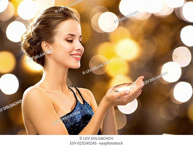 people, holidays, jewelry and luxury concept - smiling woman in evening dress and diamond earrings over lights background