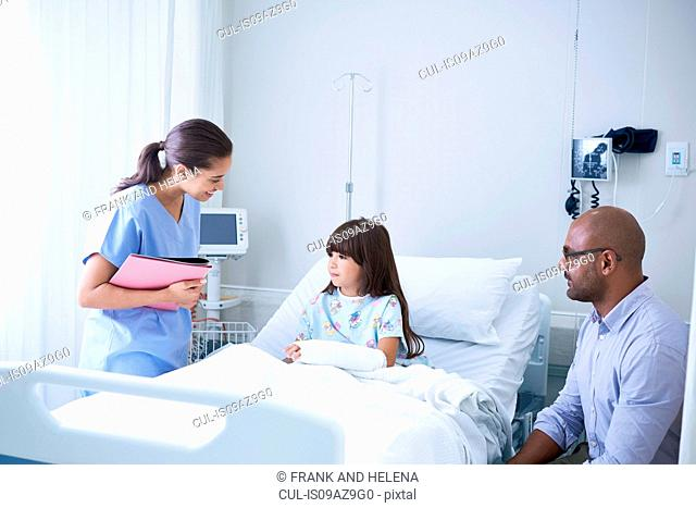 Female nurse explaining to girl patient with arm plaster cast in hospital children's ward with father