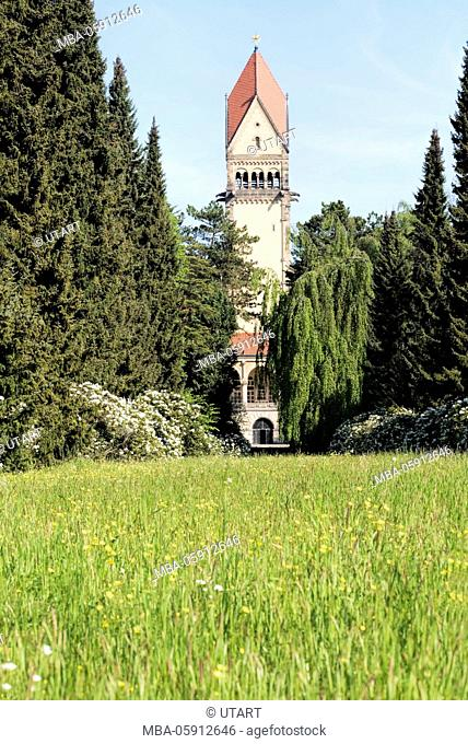 South cemetery of Leipzig, tower of the crematory picturesquely between meadow and trees
