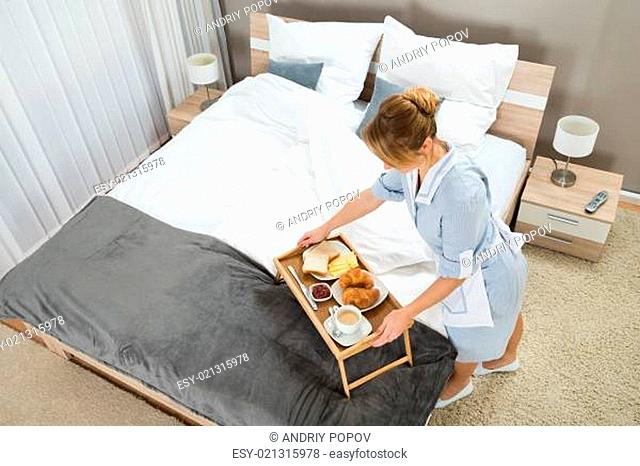 High Angle View Of Beautiful Maid With Breakfast Keeping On Table Tray In Hotel Room