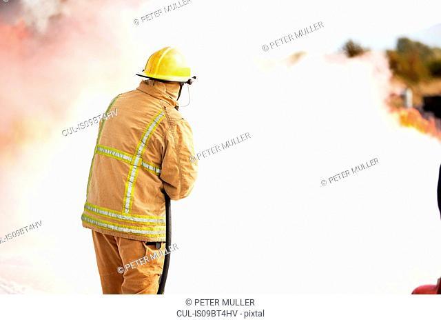Firemen training, fireman spraying firefighting foam at training facility
