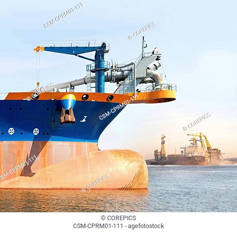 Bow of an industrial ship, with large cranes unloading raw materials from a tanker in the background on a sunny day