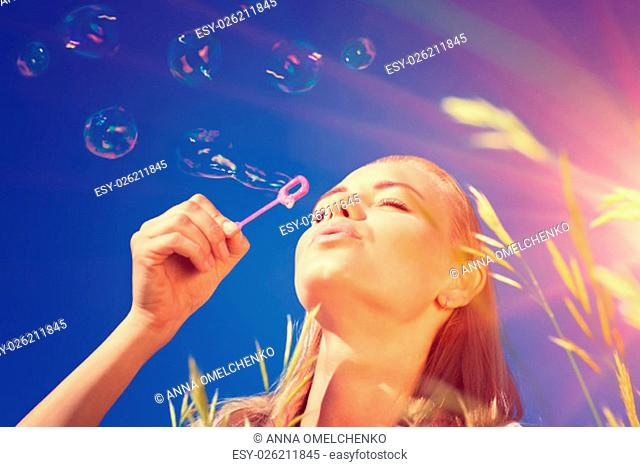 .Portrait of pretty woman with pleasure blowing soap bubbles over blue sky background, having fun outdoors in sunny day