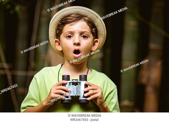 Young boy holding binoculars and making shocked expression
