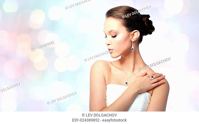 beauty, jewelry, people and luxury concept - beautiful asian woman or bride with earring, finger ring and pendant over holidays lights background
