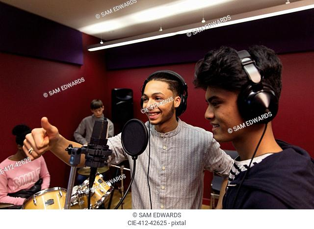 Smiling teenage musicians recording music, singing in sound booth