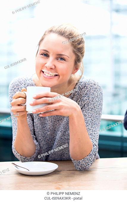 Portrait of young woman drinking coffee, milk moustache on upper lip, smiling