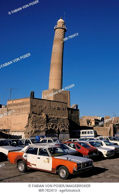 Beat up old cars parked in front of the leaning crooked minaret of the Nuriya Mosque (Jami an-Nuri, built 1148), Mosul, Iraq, Middle East