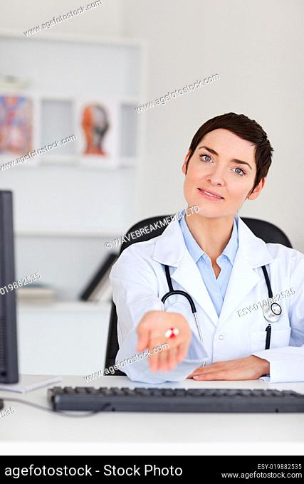 Portrait of a doctor showing pills