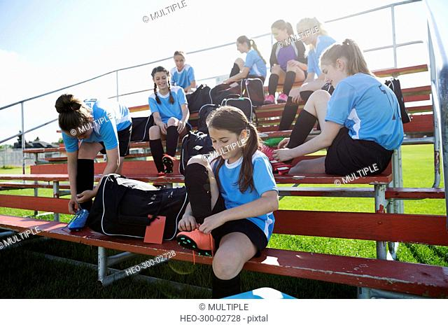 Middle school girl soccer team preparing putting on shoes on bleachers