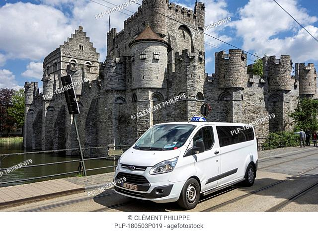 Taxi riding in front of the Gravensteen / Castle of the Counts in the historic city centre of Ghent, East Flanders, Belgium