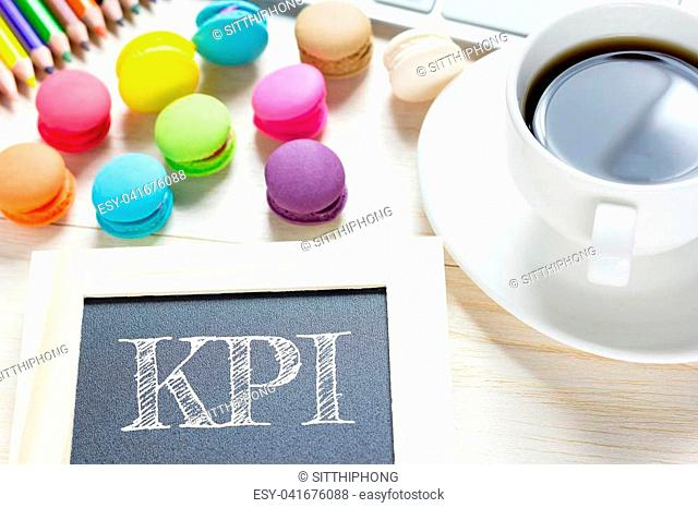 Concept KPI message on wood boards.Macaroons and glass coffee on table. Vintage tone