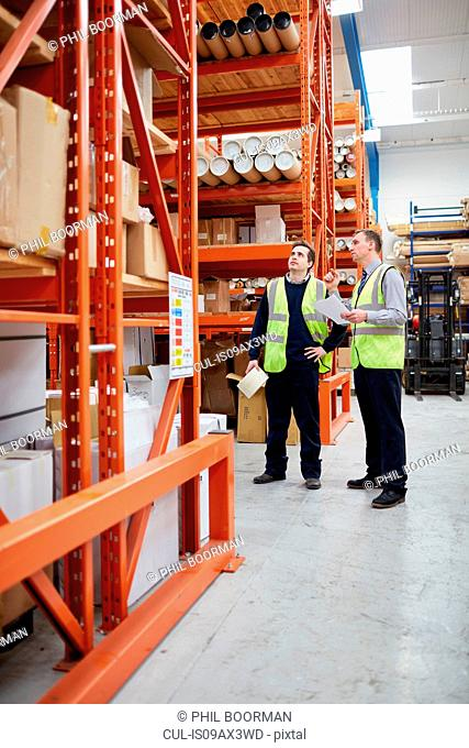 Manager and male factory worker checking paperwork in factory warehouse