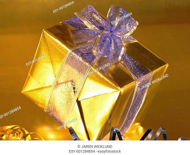 Elegant gold present with blue ribbons on gold background