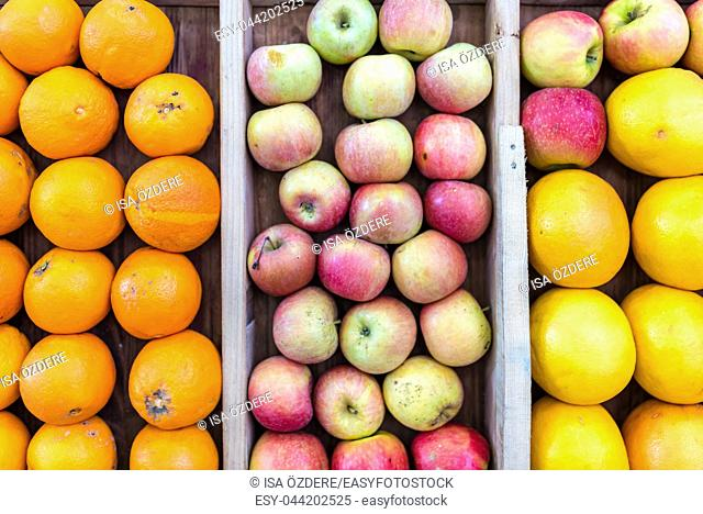 apples,grapefruits and oranges are sold in wooden crates on market stall