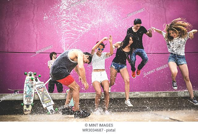 A group of young people jumping while being sprayed with water