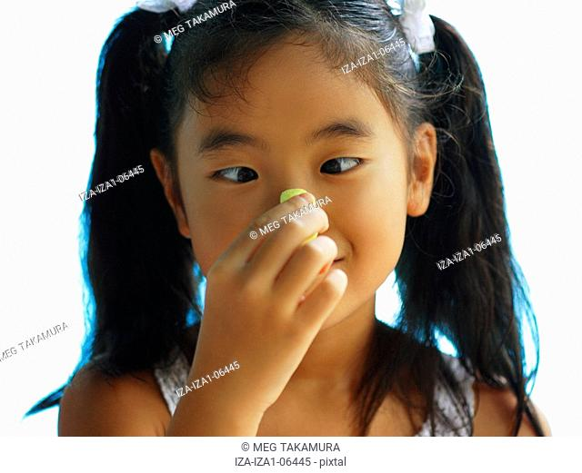 Close-up of a girl holding a candy on her nose