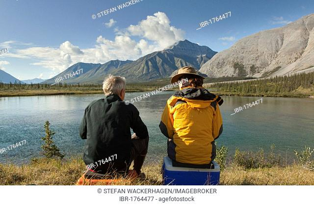 Couple, man and woman, sitting on the shore, enjoying panorama, view, Wind River Valley, Northern Mackenzie Mountains, Yukon Territory, Canada