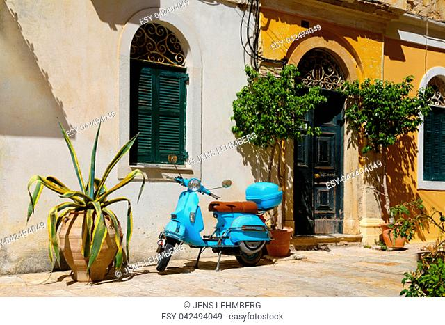 Mediterranean house with scooter parking in front of it