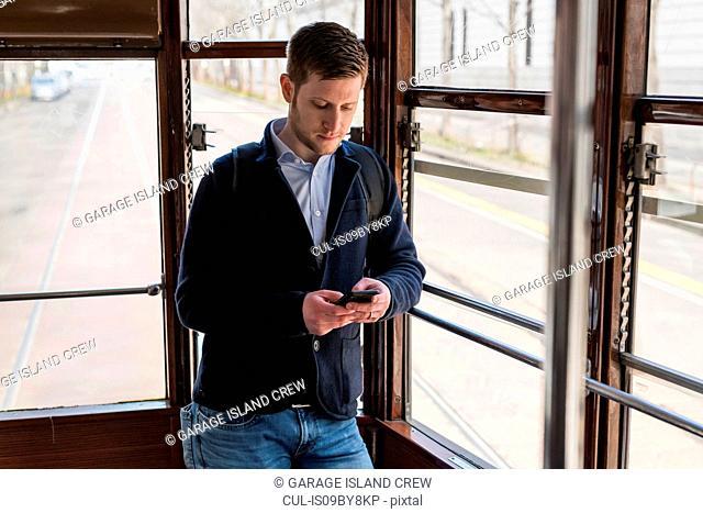 Man using smartphone inside tram, Milan, Lombardia, Italy