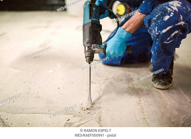 Bricklayer removing irregularities on floor screed with jackhammer