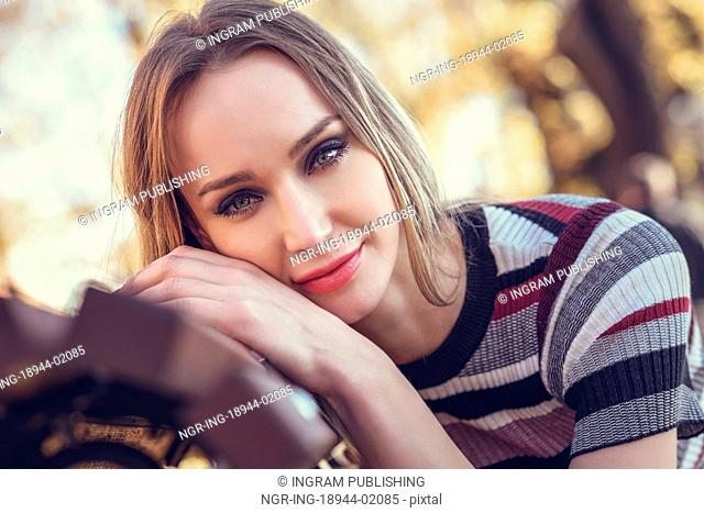 Close-up portrait of young blonde woman sitting on a bench in the street of a park with autumn colors. Beautiful girl with blue eyes in urban background wearing...