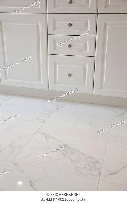 White cabinets with marble floor in the bathroom at home