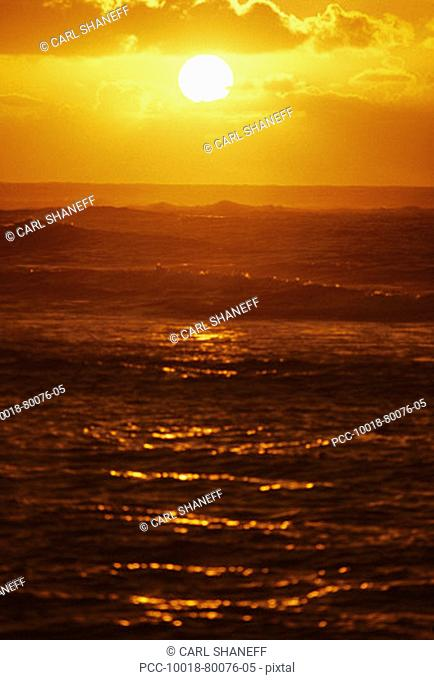 Sunball in cloudy yellow sky above red reflecting ocean