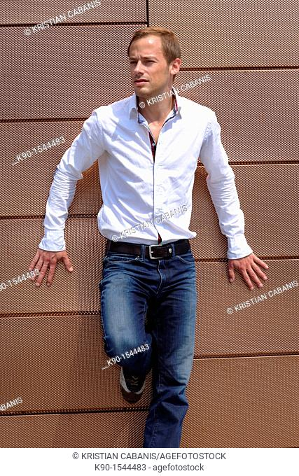 Young caucasian man, full body, with white shirt and jeans, looking friendly into the far distance while leaning at a metal wall, Hamburg, Germany, Europe