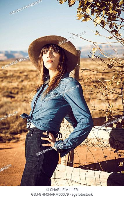 Portrait of Young Adult Woman in Cowboy in Rural Setting
