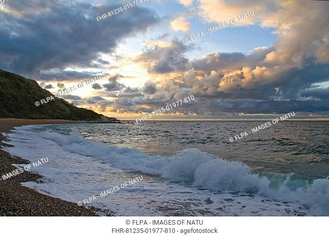 View over English Channel with cumulus clouds and waves breaking on shingle beach at sunrise, Ringstead, Dorset, England, october