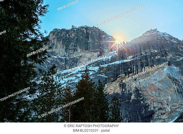 Sun rising over rocky landscape, Yosemite, California, United States