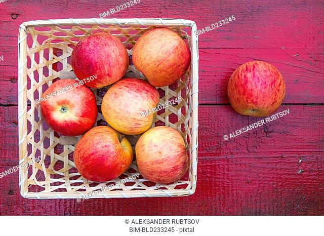 Close up of basket of red apples on red wooden table