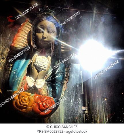 The sun is reflected in an altar to Our Lady of Guadalupe in Colonia Roma, Mexico City, Mexico