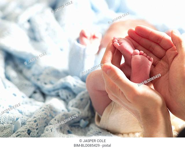 Large hands holding tiny newborn's feet