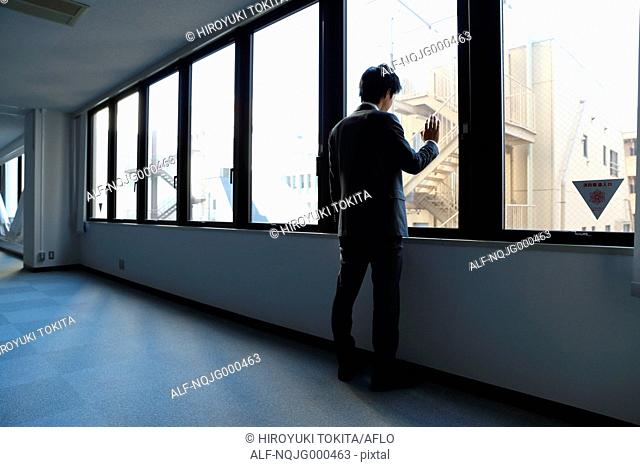 Japanese businessman looking out of the window in empty office