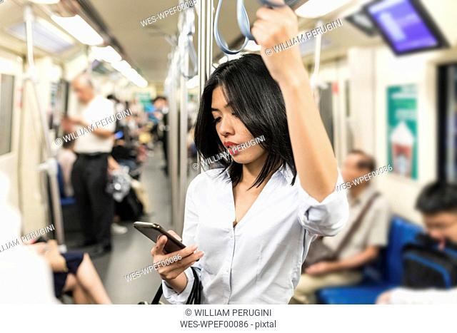 Businesswoman using cell phone in the subway